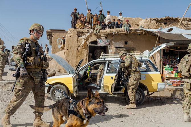 Sargento do Exército, Terry Young e seu Pastor Alemão, Wero, procuram explosivos na cidade de Candaar, no Afeganistão.  (Foto: Reprodução / Adam Ferguson / National Geographic)