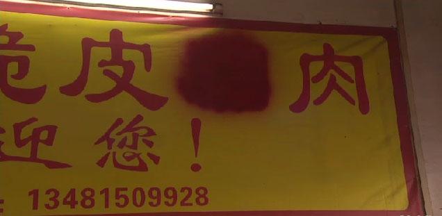 """A palavra """"cachorro"""" apagada de banner. Publicidade de carne canina foi banida pelo governo chinês, apesar de ser possível encontrar cartazes no local. Foto: Reprodução/CNN"""