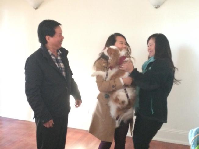 Nina Pham abraçando seu cão Bentley, ao lado de seus pais. (Foto: Reprodução / Twitter / Sana Syed)