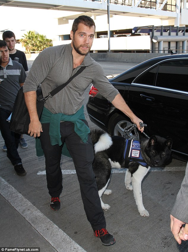 Henry Cavill chegando ao aeroporto com seu cachorro. (Foto: Reprodução / Daily Mail UK)