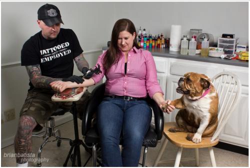 Mulher fazendo tatuagem e recebendo o apoio de sua cachorra resgatada. (Foto: Reprodução / brimanphoto.com)