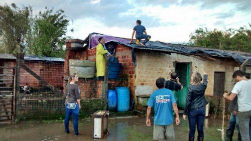Cobrindo o telhado danificado com lonas. (Foto: Reprodução / Facebook)
