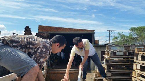 Voluntários levando madeira para cobrir o piso. (Foto: Reprodução / Facebook)