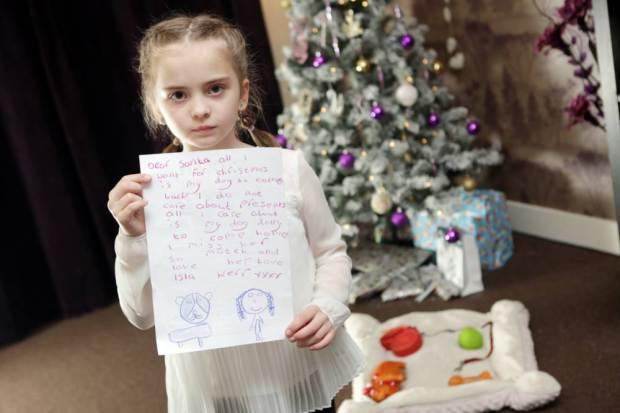 Isla mostrando a cartinha que escreveu para o Papai Noel. (Foto: Reprodução / Metro UK)
