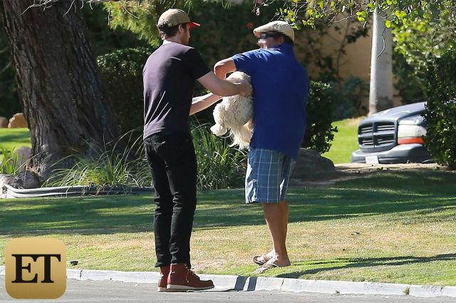 O ator entregando o cão ao tutor. (Foto: Reprodução / Entertainment Tonight)