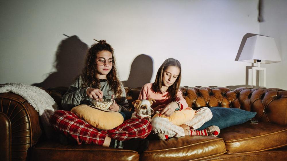 Duas garotas assistindo tv com seu cachorro ao meio